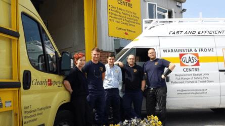 five staff in front of vans