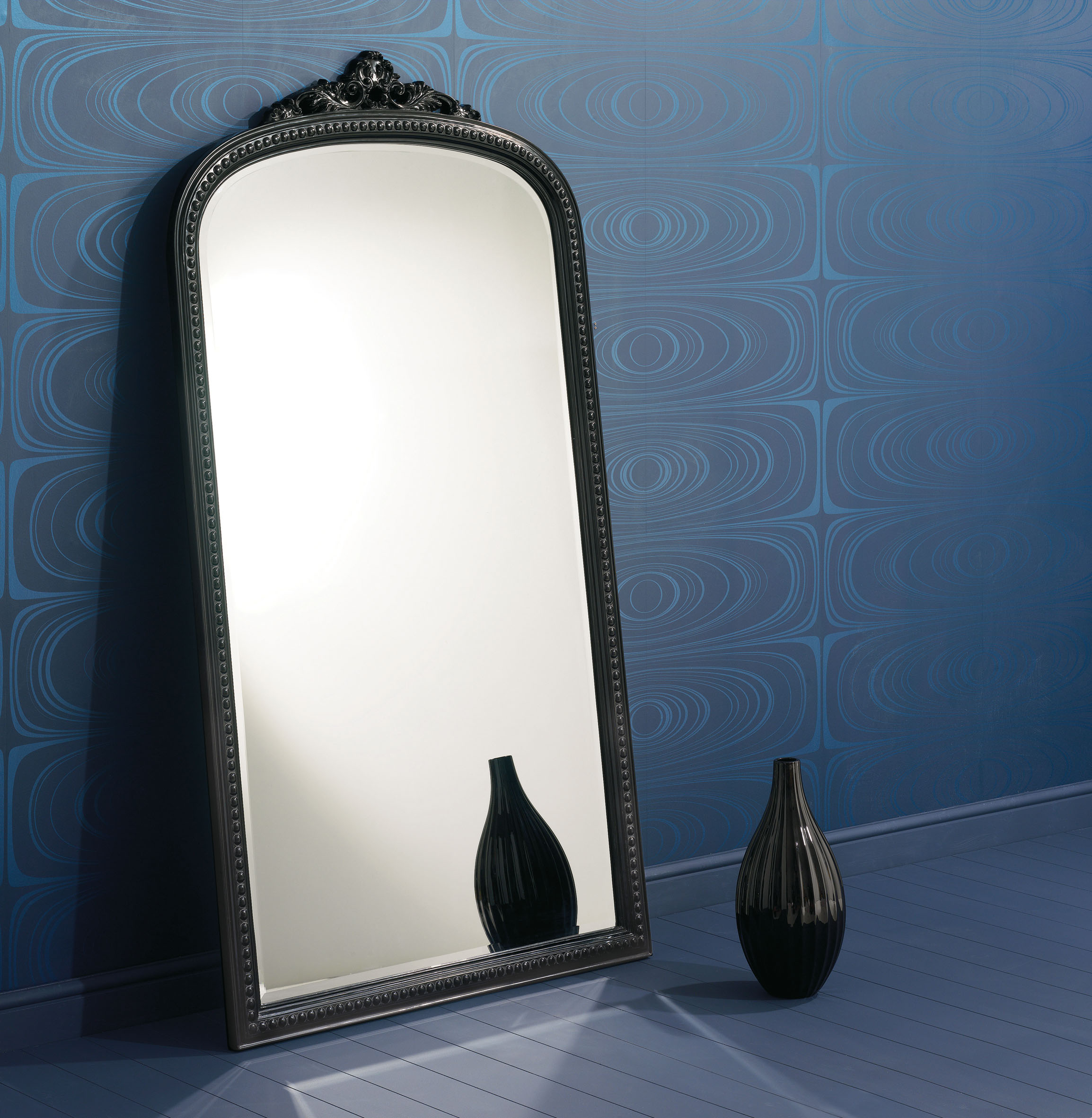 blue wall with large mirror and vase