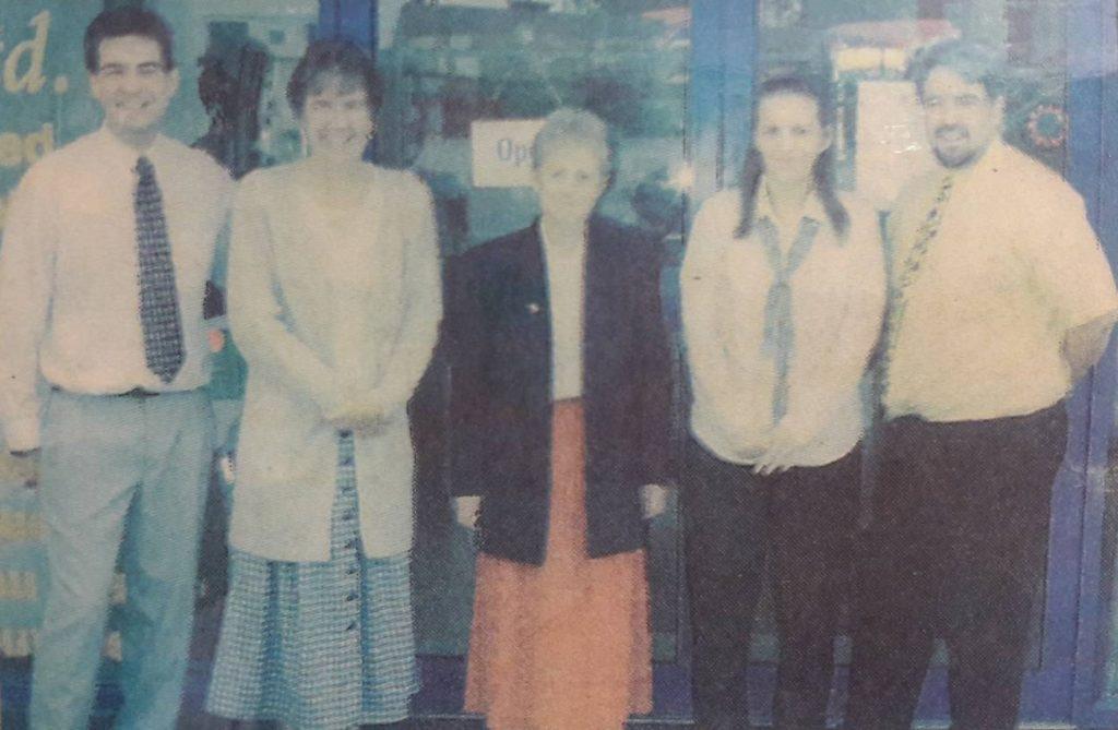 five staff outside shop