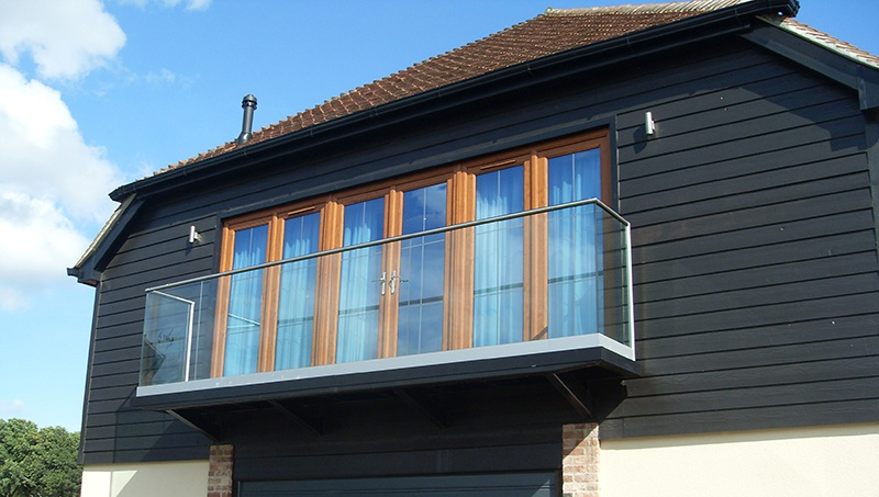 glass balcony off painted timber house