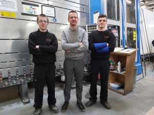 Three people standing in a factory